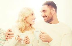 Glückliches Paar mit Schalen Tee zu Hause trinkend Stockbild