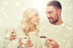 Glückliches Paar mit Schalen Tee zu Hause trinkend Stockfotografie
