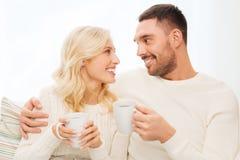 Glückliches Paar mit Schalen Tee zu Hause trinkend Stockbilder