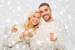 Glückliches Paar mit Schalen Tee zu Hause trinkend Lizenzfreie Stockbilder