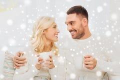 Glückliches Paar mit Schalen Tee zu Hause trinkend Lizenzfreie Stockfotos