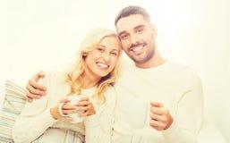 Glückliches Paar mit Schalen Tee zu Hause trinkend Lizenzfreie Stockfotografie