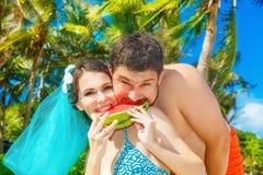 Glückliches Paar mit Scheibe der Wassermelone auf dem Strand von einem tropischen Stockbild