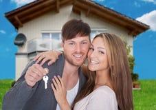 Glückliches Paar mit Schlüssel gegen neues Haus Stockbilder