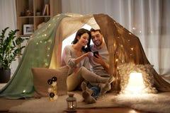 Glückliches Paar mit Smartphone im Kinderzelt zu Hause lizenzfreies stockbild