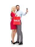Glückliches Paar mit Smartphone und Einkaufstasche Stockfotografie