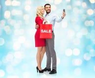 Glückliches Paar mit Smartphone und Einkaufstasche Lizenzfreie Stockfotos