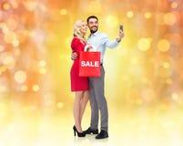 Glückliches Paar mit Smartphone und Einkaufstasche Lizenzfreie Stockfotografie