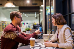 Glückliches Paar mit Smartphone und Getränke am Café lizenzfreie stockfotografie