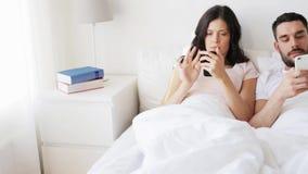 Glückliches Paar mit Smartphones im Bett stock footage