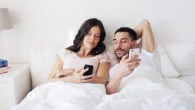 Glückliches Paar mit Smartphones im Bett stock video