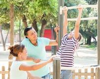 Glückliches Paar mit Training des jugendlichen Sohns ziehen an Stange hoch Stockfotografie