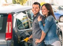 Glückliches Paar an pumpendem Benzin der Brennstoffstation an der Gaspumpe lizenzfreies stockbild