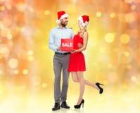Glückliches Paar in Sankt-Hüten mit rotem Verkaufszeichen Stockbild