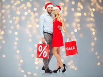 Glückliches Paar in Sankt-Hüten mit roten Einkaufstaschen Stockfotografie
