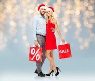 Glückliches Paar in Sankt-Hüten mit roten Einkaufstaschen Lizenzfreies Stockbild
