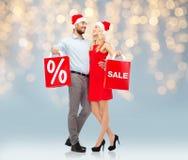 Glückliches Paar in Sankt-Hüten mit roten Einkaufstaschen Lizenzfreies Stockfoto