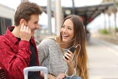 Glückliches Paar von den Reisenden, die Musik an den Feiertagen teilen Stockbilder