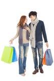 Glückliches Paar, welches das Einkaufen lokalisiert auf Weiß tut Lizenzfreie Stockfotos