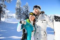 Glückliches Paar, welches das Panorama von Bergen im Schnee bewundert Lizenzfreie Stockfotos