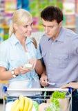 Glückliches Paar, welches die Einkaufsliste und die ausgesuchten Produkte bespricht Stockfotos