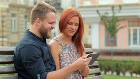 Glückliches Paar, welches die Tablette im Freien verwendet stock video footage