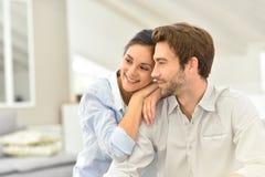 Glückliches Paar zu Hause, das auf Sofa sitzt Lizenzfreies Stockbild