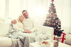 Glückliches Paar zu Hause mit Weihnachtsbaum lizenzfreie stockfotos