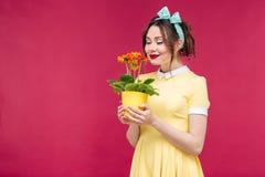 Glückliches Pinupmädchen, das orange Blume im Topf stamding und gerochen worden sein würden lizenzfreie stockfotografie