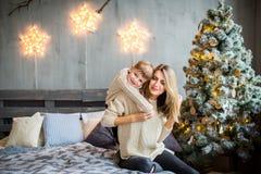 Glückliches Porträt der Mutter und des Sohns, die auf neues Jahr ` s Hintergrund spielen stockbilder