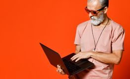 Glückliches Porträt des modischen Pensionärs den Gebrauch des neuen Laptops genießend stockbilder