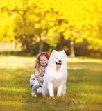 Glückliches positives Kind und Hund, die Spaß draußen hat Stockbilder