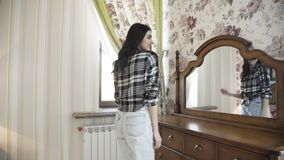 Glückliches positives Mädchen, das am Spiegel im luxuriösen Schlafzimmer aufwirft 4K stock video footage