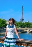 Glückliches Reisemädchen auf der Brücke Pont Alexandre III mit Eiffelturm in Paris Stockfotografie