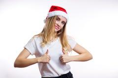 Glückliches reizend blondes Mädchen in rotem Sankt-Hut und -t-Shirt zeigt sich Daumenzeichen und Lächeln an der Kamera auf weißem stockfotos