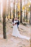 Glückliches romantisches eben verheiratetes Paar, das im Herbstkiefernwald sich hält Lizenzfreie Stockfotos