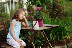 Glückliches romantisches Kindermädchen, das im Abendsommergarten träumt Lizenzfreies Stockbild