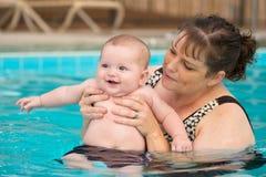 Glückliches Säuglingsbaby, das sein erstes Schwimmen genießt Stockbild
