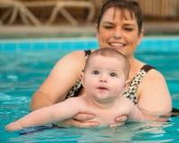 Glückliches Säuglingsbaby, das sein erstes Schwimmen genießt Stockbilder