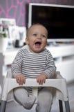 Glückliches Säuglingskind im Babystuhl Stockfotos