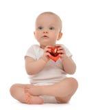 Glückliches Säuglingskinderbabykleinkind, das rotes Herz hält Stockbilder