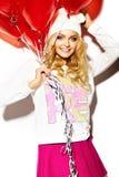 Glückliches süßes nettes lächelndes blondes Mädchen in der bunten Kleidung Stockfotografie