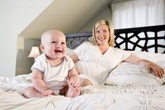 Glückliches Schätzchen, das auf Bett mit Mutter sitzt Stockfoto