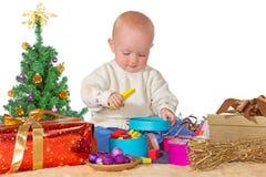 Glückliches Schätzchen, das mit einem Weihnachtsgeschenk spielt lizenzfreie stockfotografie