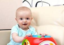 Glückliches Schätzchen mit Spielzeug Stockfotos