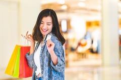 Glückliches schönes Asiatinlächeln an der Kreditkarte, Griffeinkaufstaschen Shopaholic-Leute, Sonderangebot-Preiskonzept des Einz stockfoto