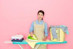 Glückliches schönes asiatisches Mädchen, welches das Bügeln tut Lizenzfreie Stockbilder
