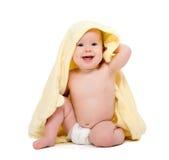 Glückliches schönes Baby im gelben Tuch lokalisiert Stockfotografie