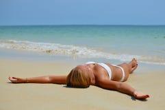 Glückliches schönes blondes Mädchen, das auf dem Strand liegt Stockfotos