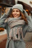 Glückliches schönes junges Mädchen mit einem Lächeln in einem grauen modischen Mantel stockbild